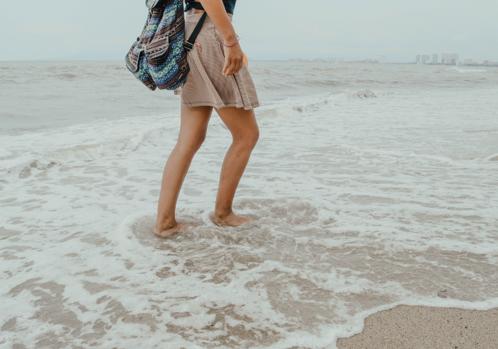 Woman walking on the beach to stop living in the past.